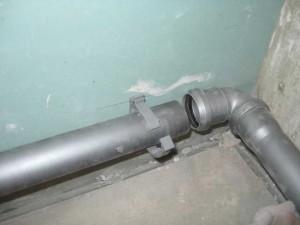 На фото - крепление канализационных труб к стене, ura-remontu.ru