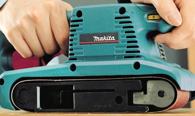 На фото - ленточная шлифовальная машинка Makita 9910